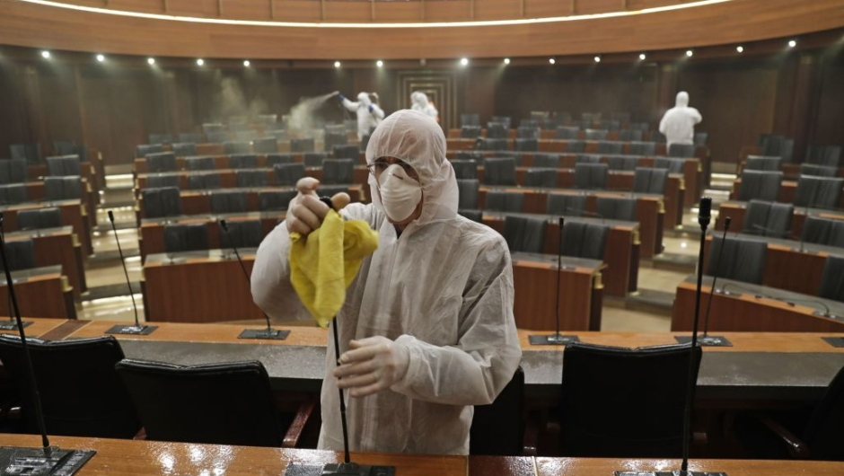 TOPSHOT - Sanitary workers disinfect the desks and chairs of the Lebanese Parliament in central Beirut on March 10, 2020 amid the spread of coronavirus in the country. (Photo by ANWAR AMRO / AFP) (Photo by ANWAR AMRO/AFP via Getty Images)