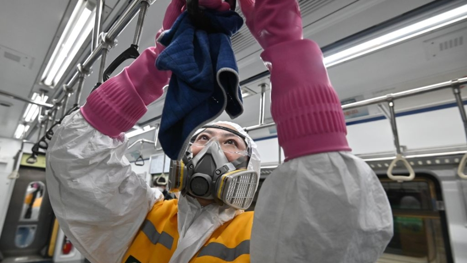 TOPSHOT - A worker wearing protective gear disinfects a train to help prevent the spread of the COVID-19 coronavirus, at Seoul Metro Gunja Train Depot in Seoul on March 11, 2020. - South Korea announced its first rise in new coronavirus cases for five days on March 11, following a run of declines that have raised hopes the outbreak is coming under control. A total of 242 infections were confirmed on March 10 taking the South's total to 7,755. (Photo by Jung Yeon-je / AFP) (Photo by JUNG YEON-JE/AFP via Getty Images)