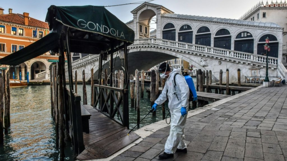 TOPSHOT - An employee of the municipal company Veritas sprays disinfectant in public areas at the Rialto Bridge in Venice on March 11, 2020, as part of precautionary measures against the spread of the new coronavirus COVID-19, a day after Italy imposed unprecedented national restrictions on its 60 million people Tuesday to control the deadly COVID-19 coronavirus. (Photo by MARCO SABADIN / AFP) (Photo by MARCO SABADIN/AFP via Getty Images)