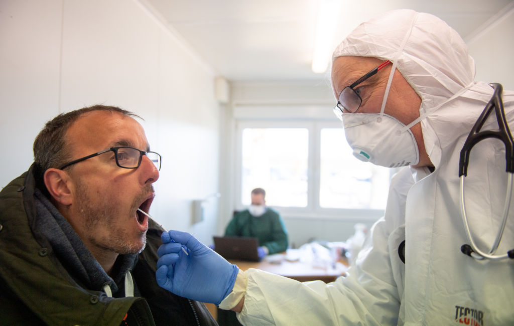 PAPENBURG, GERMANY - MARCH 23: Local doctor Volker Eissing peers into the throat of a patient while checking for flu and also to take a throat swab sample for coronavirus testing at Eissing's temporary office located in a container on March 23, 2020 in Papenburg, Germany. Eissing is using the container, located on a parking lot, in order to avoid possible coronavirus exposure for his colleagues at his regular practice. Around 50 people a day come to be tested for coronavirus and the disease the virus causes, COVID-19. Germany is struggling to reign in the spread of the coronavirus, which so far has infected at least 24,000 people nationwide. (Photo by David Hecker/Getty Images)