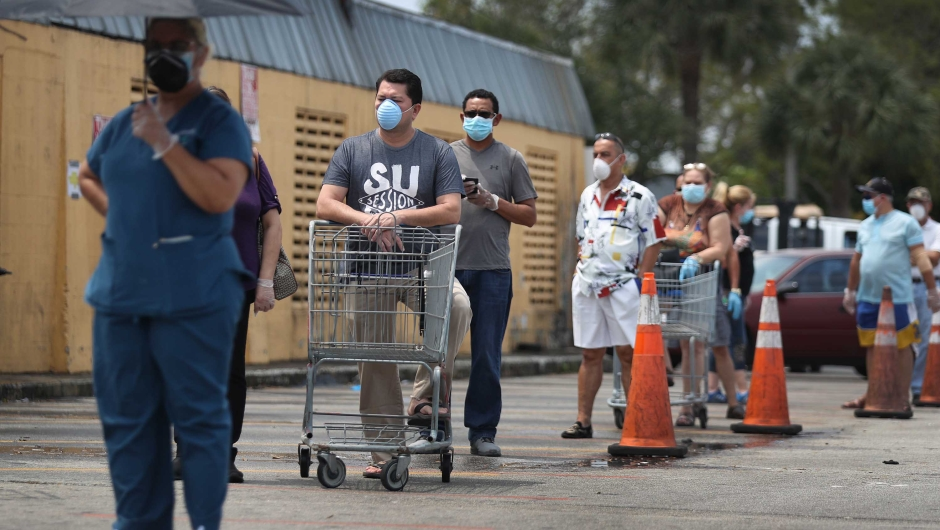 MIAMI, FLORIDA - APRIL 13: Customers wearing masks line up to shop at the Presidente Supermarket on April 13, 2020 in Miami, Florida. The employees at Presidente Supermarket, like the rest of America's grocery store workers, are on the front lines of the coronavirus pandemic, helping to keep the nation's residents fed. (Photo by Joe Raedle/Getty Images)