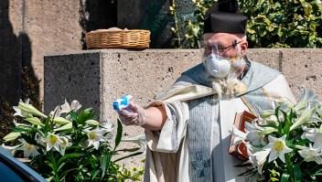 Un sacerdote bendice a distancia con pistola de agua