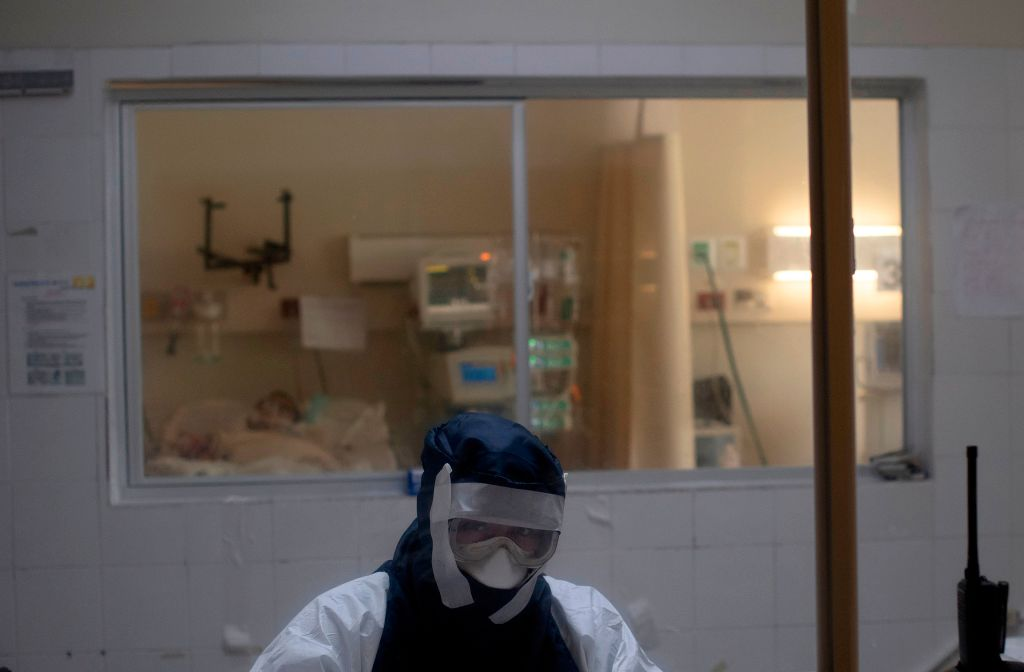 "A doctor remains in an observation cabin in front of a patient infected with the novel coronavirus COVID-19, in the intensive care unit of the San Rafael Hospital in Santa Tecla, La Libertad, just 10 km from the Salvadorean capital San Salvador, on May 16, 2020. - The San Rafael Hospital, which has been assigned to care for 100 COVID-19 patients whose cases range from ""severe to critical,"" is leading in their recovery, and part of the success, according to hospital director Yeerles Luis Ramirez, has been early treatment. (Photo by Yuri CORTEZ / AFP) (Photo by YURI CORTEZ/AFP via Getty Images)"