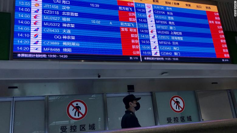 A man wearing a facemask stands under a screen showing mostly cancelled flights at Tianhe airport in Wuhan in China's central Hubei province on January 23, 2020. - China banned trains and planes from leaving a major city at the centre of a virus outbreak on January 23, seeking to seal off its 11 million people to contain the contagious disease that has claimed 17 lives, infected hundreds and spread to other countries. (Photo by Leo RAMIREZ / AFP) (Photo by LEO RAMIREZ/AFP via Getty Images)
