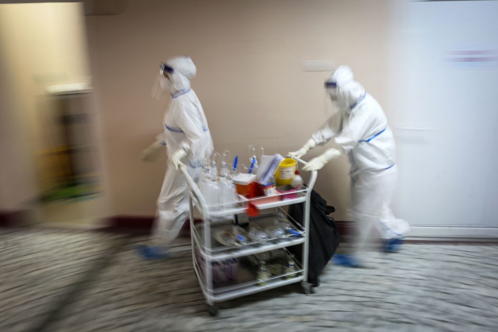 """TOPSHOT - Medical workers bring medications to patients suffering from coronavirus disease (COVID-19) inside the Institute for Orthopaedic Surgery """"Banjica"""", recently transformed to a COVID hospital, in Belgrade on July 14, 2020. - A candidate for the European Union, this small Balkan country is experiencing a resurgence of the pandemic, which has sparked several evenings of violent demonstrations to denounce the government's management of the health crisis. With 300 new cases now detected every day, Serbia is approaching April levels, at the peak of the first wave. (Photo by Oliver BUNIC / AFP) (Photo by OLIVER BUNIC/AFP via Getty Images)"""