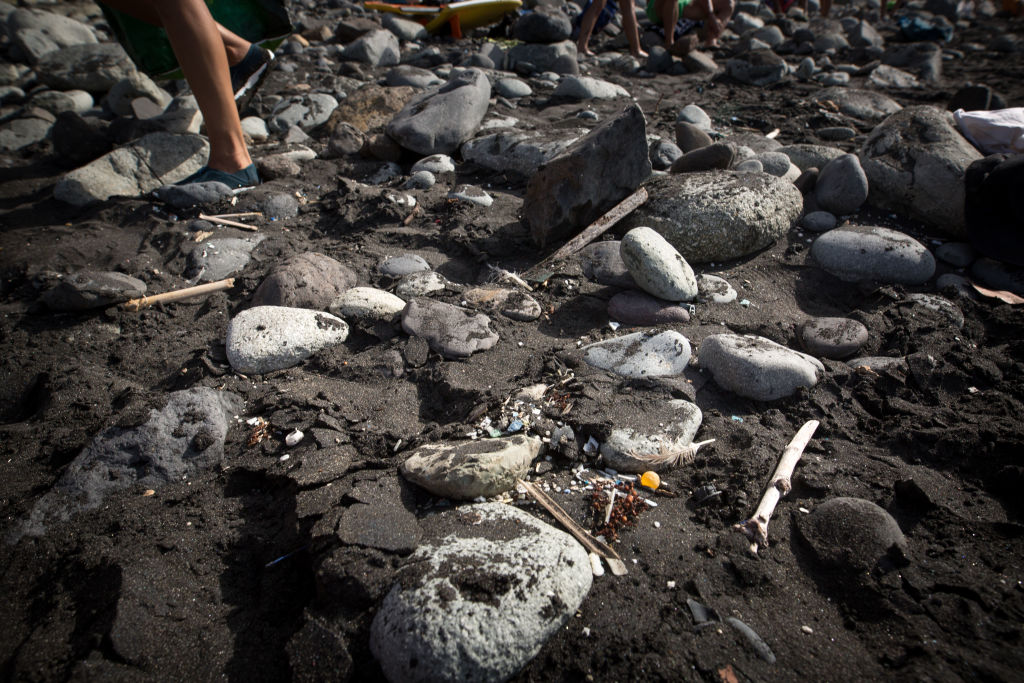 A volunteer of the NGO 'Canarias Libre de Plasticos' (Canary Islands free of plastics) carries out a collection of microplastics and mesoplastic debris to clean the Almaciga Beach, on the north coast of the Canary Island of Tenerife, on July 14, 2018. (Photo by DESIREE MARTIN / AFP) (Photo credit should read DESIREE MARTIN/AFP via Getty Images)