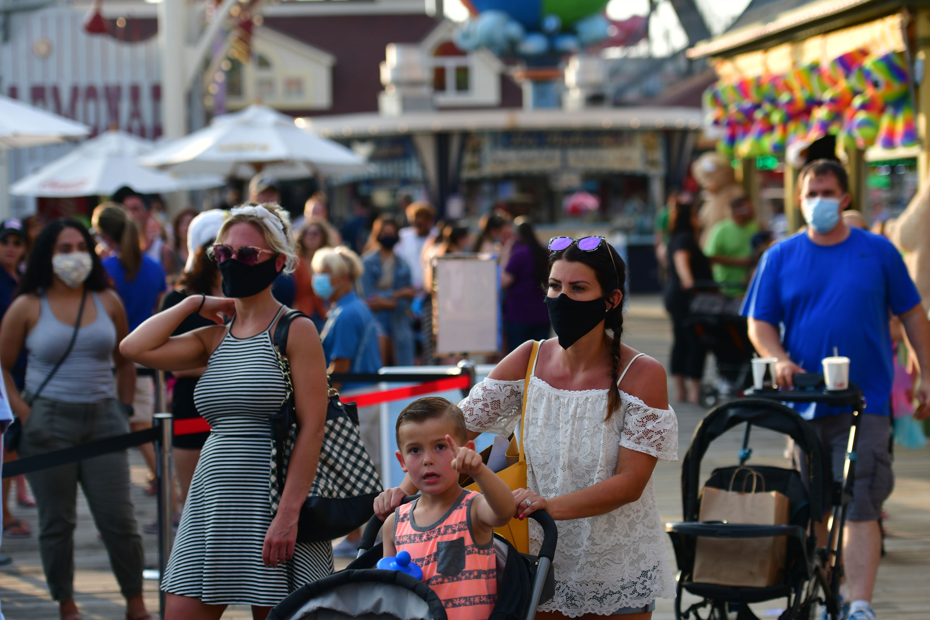 WILDWOOD, NJ - JULY 03: A family waits in line at the entrance to an amusement pier on July 3, 2020 in Wildwood, New Jersey. New Jersey beaches have reopened for the July 4th holiday as some coronavirus restrictions have been lifted, along with casinos, amusement rides and water parks at limited capacity. (Photo by Mark Makela/Getty Images)