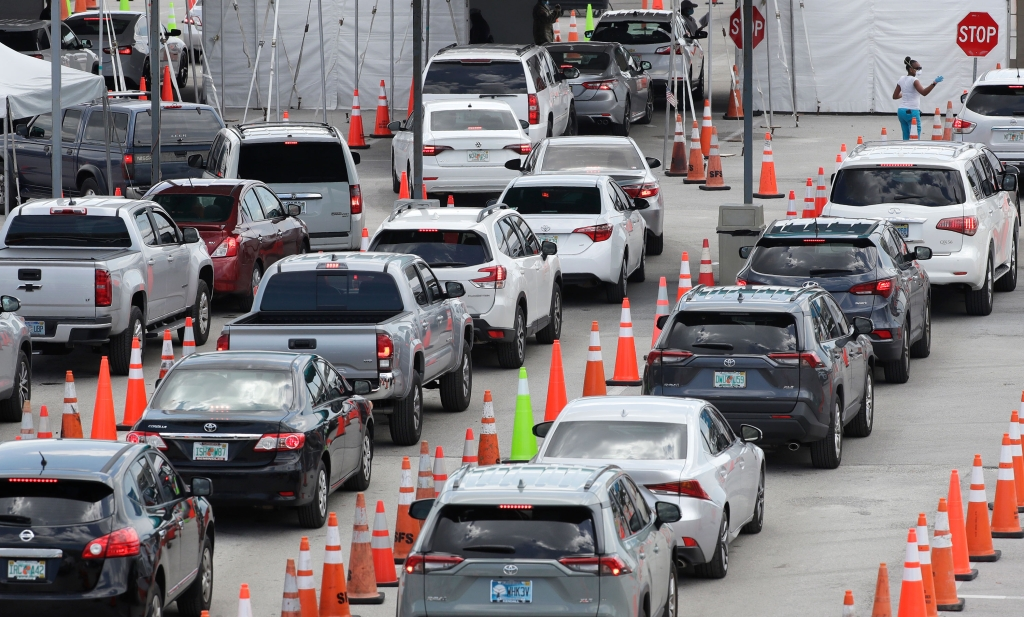 Vehicles wait in line at a drive-thru COVID-19 testing site outside Hard Rock Stadium, Wednesday, July 8, 2020, in Miami Gardens, Fla. Florida is one of the nation's hot spots for coronavirus. Almost 10,000 confirmed cases were added Wednesday, bringing its total since March 1 to nearly 224,000. Almost 4,000 people have died, including 48 reported by the state Wednesday. (AP Photo/Wilfredo Lee)