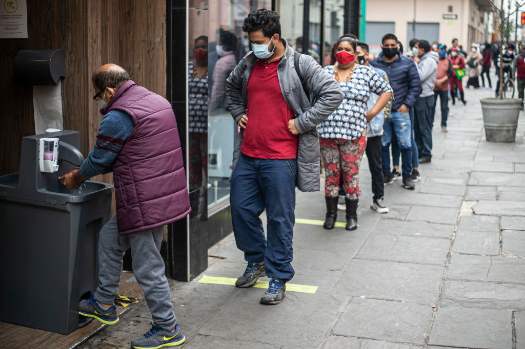 Customers disinfect their hands before entering a store in downtown Lima on July 1, 2020. - Peru began a gradual process of deconfinement on Wednesday to reactivate its semi-paralyzed economy, and the streets of Lima were once again filled with vehicles and people, after three and a half months of mandatory national quarantine due to the COVID-19 coronavirus pandemic. (Photo by ERNESTO BENAVIDES / AFP) (Photo by ERNESTO BENAVIDES/AFP via Getty Images)