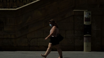 A woman wearing a face mask walks in Lerida (Lleida) on July 13, 2020. - A local court suspended a home confinement order imposed on more than 200,000 people in the Spanish region of Catalonia after an upsurge in virus cases. Catalonia officials ordered the home confinement on the city of Lerida and its surrounding areas a week after the zone had been placed under less strict lockdown. (Photo by Pau BARRENA / AFP) (Photo by PAU BARRENA/AFP via Getty Images)