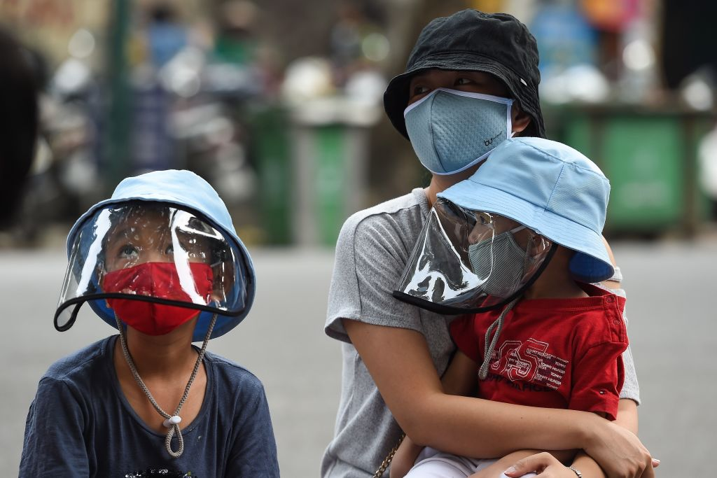 TOPSHOT - A woman waits with her children at a makeshift rapid testing centre as Vietnam records a rise in cases of the COVID-19 coronavirus in Hanoi on July 31, 2020. - Vietnam has recorded 45 news cases of COVID-19 -- its highest single daily tally since the pandemic began -- as an outbreak in the resort city of Danang erodes the country's efforts to stay virus-free. (Photo by Nhac NGUYEN / AFP) (Photo by NHAC NGUYEN/AFP via Getty Images)