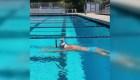 Nadadora olímpica cruza piscina con un vaso en la cabeza