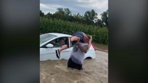Un buen samaritano saca a personas de un auto inundado