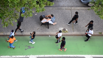 NEW YORK, NEW YORK - AUGUST 17: People sit on a traffic island in Kips Bay as the city continues Phase 4 of re-opening following restrictions imposed to slow the spread of coronavirus on August 17, 2020 in New York City. The fourth phase allows outdoor arts and entertainment, sporting events without fans and media production. (Photo by Noam Galai/Getty Images)