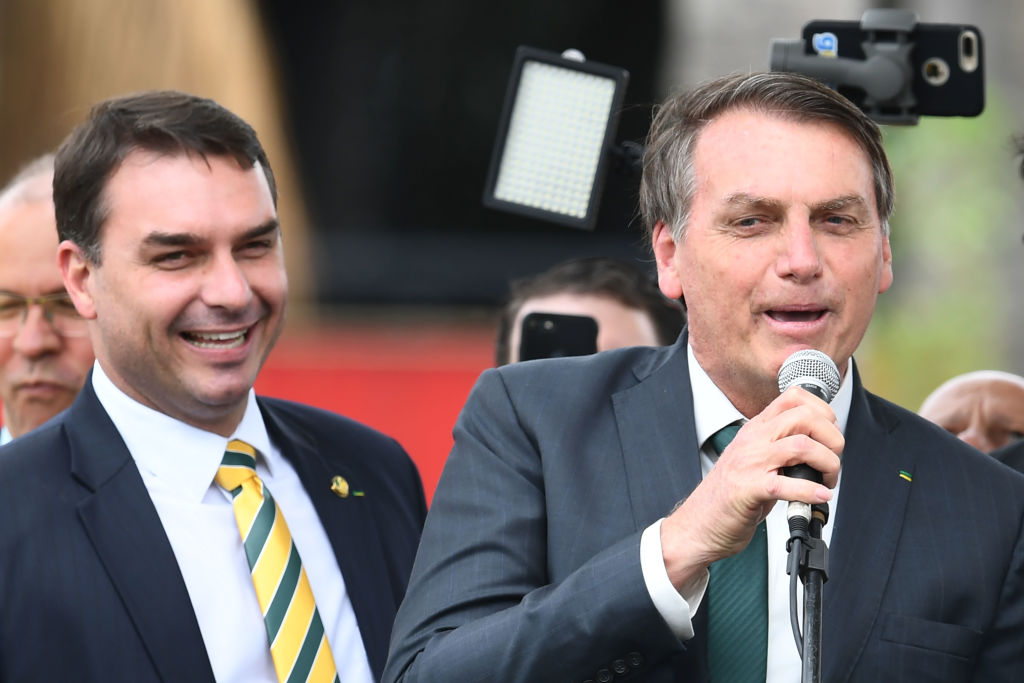 Brazilian President Jair Bolsonaro (R) speaks next to his son, senator Flavio Bolsonaro, during the launch of his new party, the Alliance for Brazil, at a hotel in Brasilia on November 21, 2019. - Bolsonaro left the Social Liberal Party after a disagreement with the party president Luciano Bivar. (Photo by EVARISTO SA / AFP) (Photo by EVARISTO SA/AFP via Getty Images)
