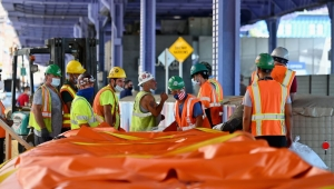 Workers set up temporary plastic flood barriers and sandbags known as 'Tiger Dams' in lower Manhattan to protect the area from flooding as tropical storm Isaias approaches New York City on August 3, 2020. - Tropical Storm Isaias was set to regain hurricane strength Monday before slamming into the US eastern seaboard, bringing life-threatening storm surges to North and South Carolina. (Photo by Angela Weiss / AFP) (Photo by ANGELA WEISS/AFP via Getty Images)