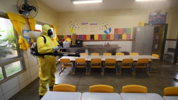 TOPSHOT - A Federal District's employee disinfects a public school as a measure against the spread of the new coronavirus in Brasilia, on August 5, 2020. - The local government has begun preparations for the safe reopening of schools in early September, as restrictions related to the COVID-19 lockdown are eased. (Photo by EVARISTO SA / AFP) (Photo by EVARISTO SA/AFP via Getty Images)