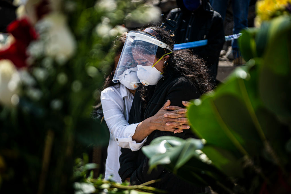 Relatives of a COVID-19 victim mourn during a funeral at a graveyard in Comas, in the northern outskirts of Lima on August 05, 2020. - The pandemic has killed at least 701,112 people worldwide since it surfaced in China late last year, according to an AFP tally at 1100 GMT on Wednesday based on official sources. (Photo by ERNESTO BENAVIDES / AFP) (Photo by ERNESTO BENAVIDES/AFP via Getty Images)