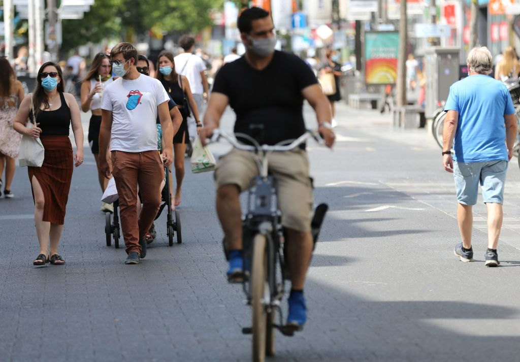 Cyclists and predestrians wear protective facemasks as they travel on a street in Antwerp on August 6, 2020, as authorities impose additional measures to attempt to curb the spread of the COVID-19 caused by the novel coronavirus