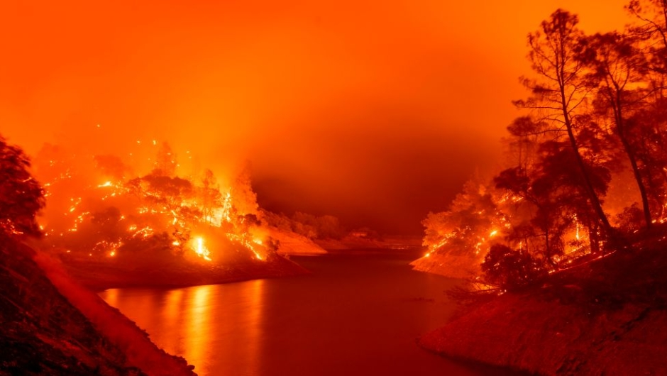 Incendios forestales california afectados hectáreas kilómetros cuadrados fotos videos TOPSHOT - In this long exposure photograph, flames consumes both sides of a segment of Lake Berryessa during the Hennessey fire in the Spanish Flat area of Napa, California on August 18, 2020. - As of the late hours of August 18, the Hennessey fire has merged with at least 7 fires and is now called the LNU Lightning Complex fires. Dozens of fires are burning out of control throughout Northern California as fire resources are spread thin. (Photo by JOSH EDELSON / AFP) (Photo by JOSH EDELSON/AFP via Getty Images)