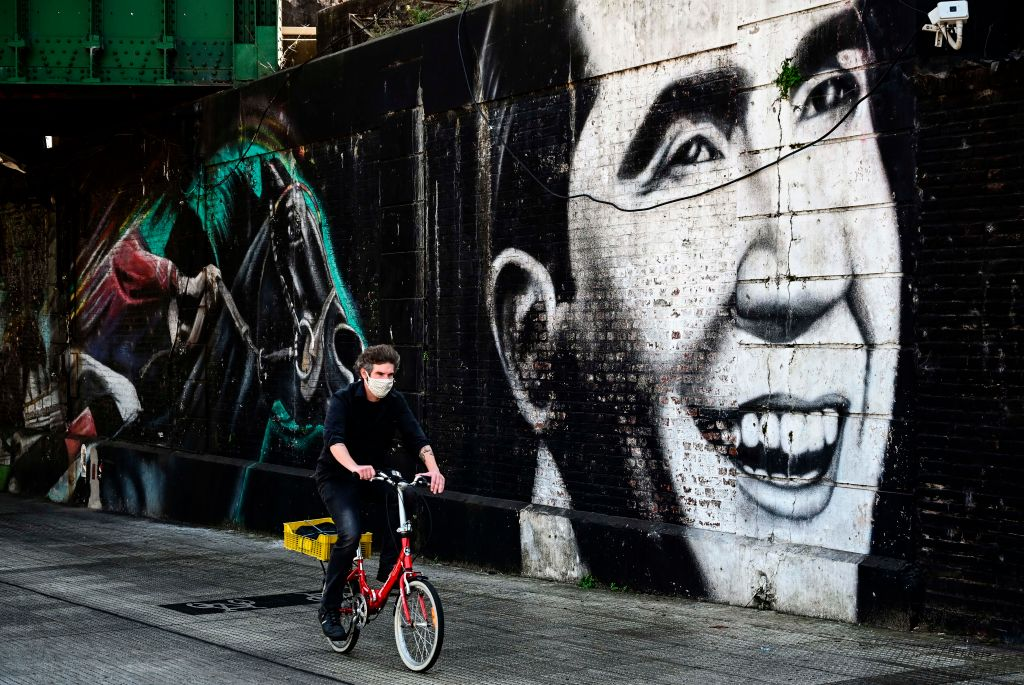 A man rides his bicycle in front of a mural with the image of tango singer Carlos Gardel, in Buenos Aires, on August 24, 2020. - Dancers from all over the world will compete from Wednesday in an unprecedented virtual tango world organized by the Buenos Aires City Hall when Argentina is confined in the worst moment of the pandemic, with more than 340,000 infections and almost 7,000 deaths per COVID-19. (Photo by RONALDO SCHEMIDT / AFP) (Photo by RONALDO SCHEMIDT/AFP via Getty Images)