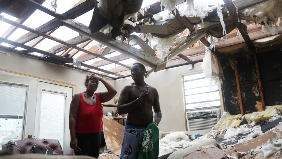 LAKE CHARLES, LOUISIANA - AUGUST 27: Latasha Myles and Howard Anderson stand in their living room where they were sitting when the roof blew off around 2:30am as Hurricane Laura passed through the area on August 27, 2020 in Lake Charles, Louisiana . The hurricane hit with powerful winds causing extensive damage to the city. (Photo by Joe Raedle/Getty Images)