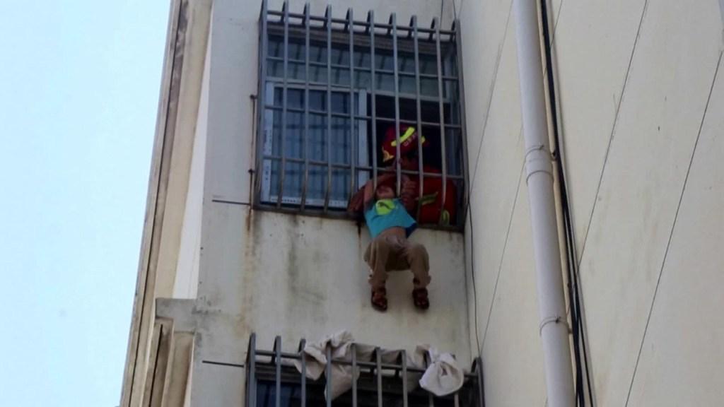 Niño queda colgado de quinto piso en China