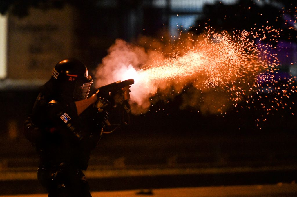 Protestas Bogotá Colombia policía abuso violencia manifestaciones enfrentamientos muertos heridosTOPSHOT - A riot police officer fires tear gas at demonstrators protesting against against police brutality in Cali, Colombia on September 10, 2020. - At least 10 people were killed and hundreds wounded after rioting broke out in the Colombian capital Bogota during protests over the death of a man repeatedly tasered by police, authorities said Thursday. (Photo by Luis ROBAYO / AFP) (Photo by LUIS ROBAYO/AFP via Getty Images)