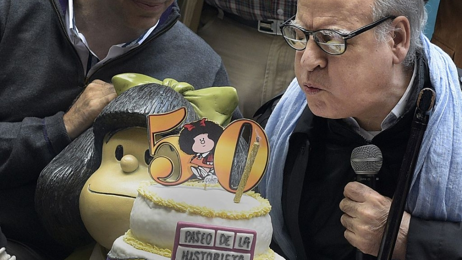 Cartoonist Joaquín Salvador Lavado known as Quino(R) blows the candle next to Mafalda the mythical rebellious and incisive girl created by him in Buenos Aires on September 29, 2014, during Mafalda 50 anniversary since its first publication. AFP PHOTO / DANIEL GARCIA (Photo credit should read DANIEL GARCIA/AFP via Getty Images)