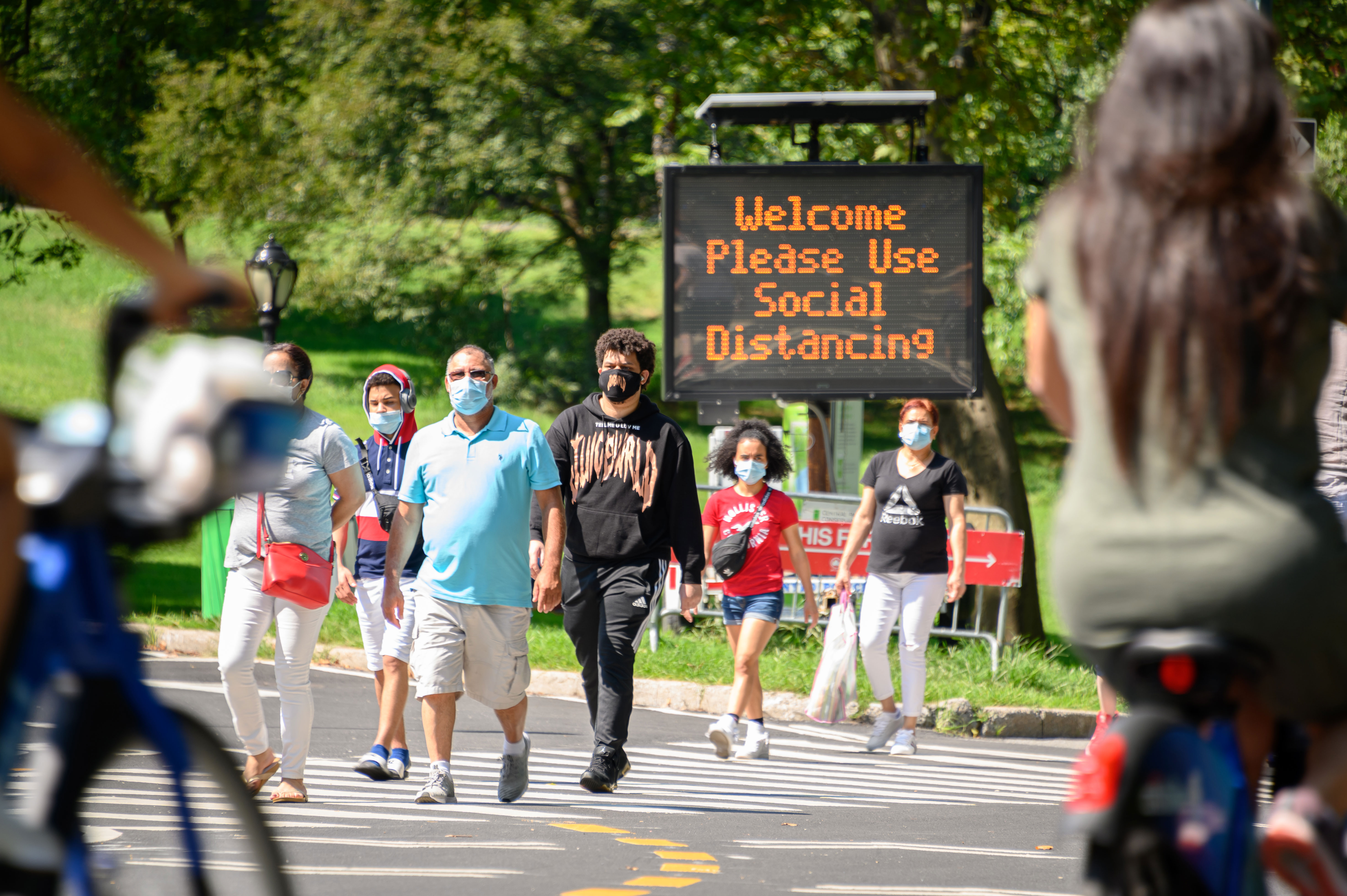 NEW YORK, NEW YORK - SEPTEMBER 06: People wear protective face masks near a social distancing sign in Central Park as the city continues Phase 4 of re-opening following restrictions imposed to slow the spread of coronavirus on September 6, 2020 in New York City. The fourth phase allows outdoor arts and entertainment, sporting events without fans and media production. (Photo by Noam Galai/Getty Images)