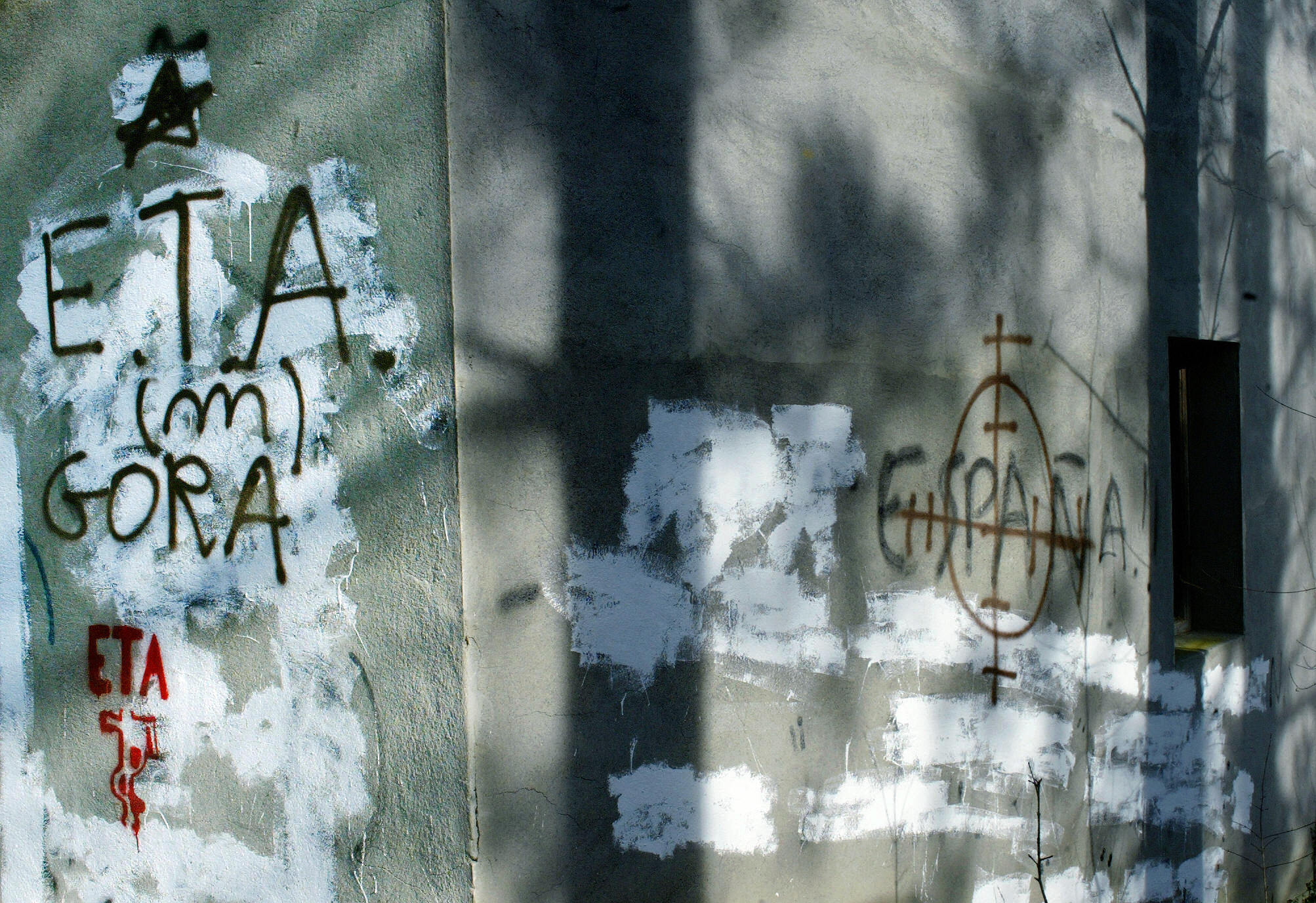 """Llodio, SPAIN: Graffiti in favor of armed Basque separatist group ETA, reading in Basque """"Up ETA"""" (L) and another bearing the """"Spain"""" in a target, are seen 25 February 2006 in the northern Spanish Basque village of Llodio. The Victims of Terrorism Association (AVT) and the opposition conservative Popular Party (PP) have called for a demonstration in Madrid 25 February 2006 today against any negotiations with ETA. The AVT and rightwing parties accuse the Socialist government of Prime Minister Jose Luis Rodriguez Zapatero of negotiating secretly with ETA, although Madrid has insisted this is not the case and that the group must lay down its arms before a dialogue can take place. AFP PHOTO / RAFA RIVAS (Photo credit should read RAFA RIVAS/AFP via Getty Images)"""