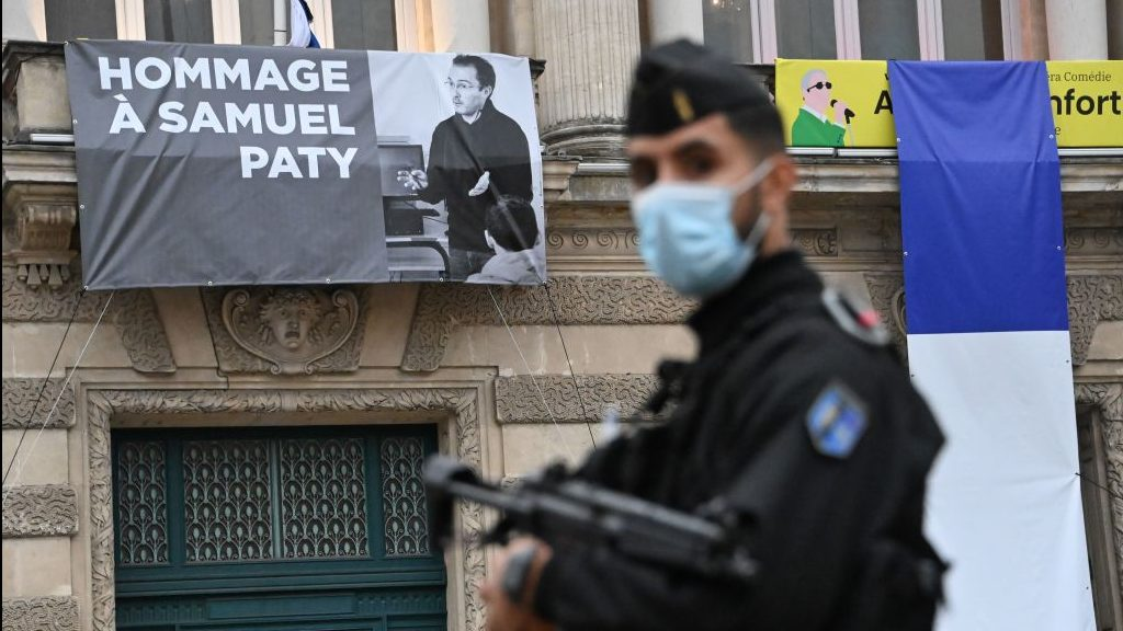 Ataque terrorista Niza A French police officer stands next to a portrait of French teacher Samuel Paty on display on the facade of the Opera Comedie in Montpellier on October 21, 2020, during a national homage to the teacher who was beheaded for showing cartoons of the Prophet Mohamed in his civics class. - France pays tribute on October 21 to a history teacher beheaded for showing cartoons of the Prophet Mohamed in a lesson on free speech, an attack that has shocked the country and prompted a government crackdown on radical Islam. Seven people, including two schoolchildren, will appear before an anti-terror judge for a decision on criminal charges over the killing of 47-year-old history teacher Samuel Paty. (Photo by Pascal GUYOT / AFP) (Photo by PASCAL GUYOT/AFP via Getty Images)
