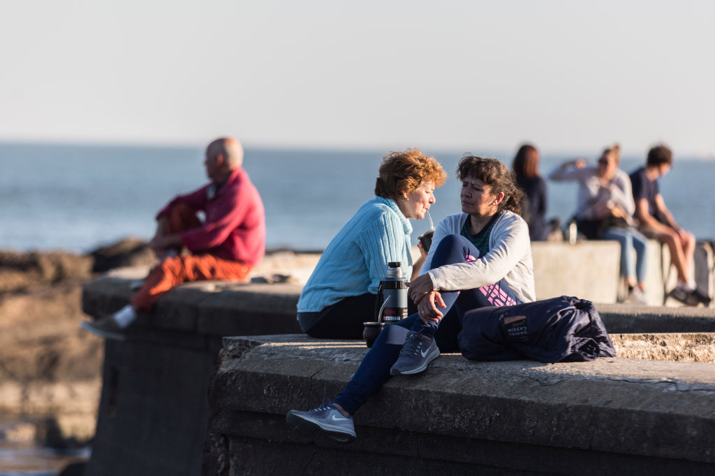 MONTEVIDEO, URUGUAY - MAY 10: Women drink mate at the promenade on May 10, 2020 in Montevideo, Uruguay. President Lacalle Pou called for a reopening of certain industries and activities, encouraging citizens to take preventive measures against COVID-19 to get back to normal. (Photo by Ernesto Ryan/Getty Images)