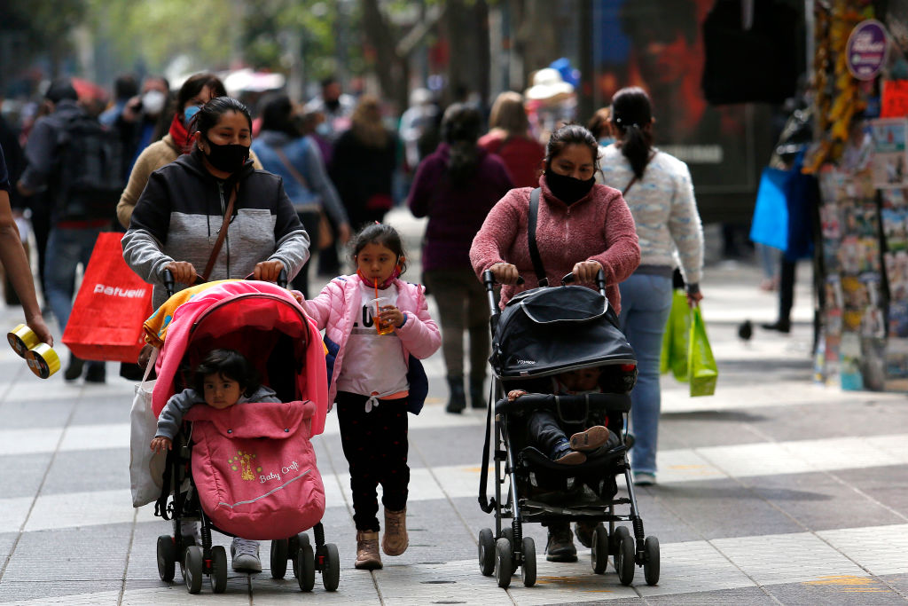 SANTIAGO, CHILE - SEPTEMBER 29: A couple of mothers wearing protective masks walk with their children in downtown as the restrictions eases on September 29, 2020 in Santiago, Chile. Most of the areas of the Metropolitan region of Santiago moved to a new phase of a five-step plan to go back to normal during the coronavirus pandemic. Chile registers over 12,690 deaths and over 460,000 positive cases since March. (Photo by Marcelo Hernandez/Getty Images)