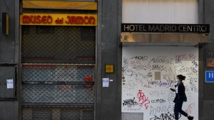 A woman walks past a closed hotel and restaurant on Gran Via, the main avenue of central Madrid, on October 16, 2020. - The coronavirus pandemic has pulverised Spain's tourism-dependent economy, with the government warning that GDP would fall by 11.2 percent this year, down from a previous prediction in May for a 9.2 percent decline. (Photo by GABRIEL BOUYS / AFP) (Photo by GABRIEL BOUYS/AFP via Getty Images)