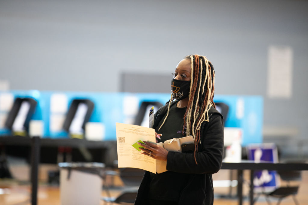 NORCROSS, GA - NOVEMBER 03: Tiffani Byron carries her completed ballot to the scanner at Lucky Shoals Park polling station on November 3, 2020 in Norcross, Georgia. After a record-breaking early voting turnout, Americans head to the polls on the last day to cast their vote for incumbent U.S. President Donald Trump or Democratic nominee Joe Biden in the 2020 presidential election. (Photo by Jessica McGowan/Getty Images)