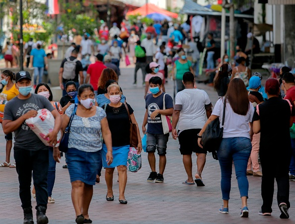 Panamá ley seca toque de queda People walk along an avenue in downtown Panama City on December 3, 2020, amid the new coronavirus pandemic. - Panama speeded up the conditioning of an unconcluded hospital and is evaluating hiring foreign medical personnel, amid constant daily records of the new coronavirus which menace to collapse the health system. (Photo by STR / AFP) (Photo by STR/AFP via Getty Images)