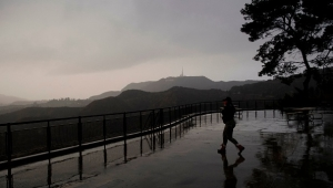 A person wears a face mask while walking to take pictures from a viewing area overlooking the Hollywood sign shrouded by clouds during heavy rains as seen from the Griffith Observatory on December 28, 2020 in Los Angeles, California. - Los Angeles residents woke up to rain today as the first major storm of the season hit the area. (Photo by Patrick T. Fallon / AFP) (Photo by PATRICK T. FALLON/AFP via Getty Images)