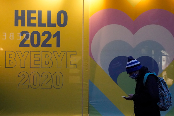 MANCHESTER, ENGLAND - DECEMBER 31: People walk past a shop display welcoming 2021 and saying goodbye to 2020 on December 31, 2020 in Manchester, England. New Year's Eve Celebrations have been curtailed in the UK this year dues to Coronavirus pandemic restrictions. With most of the UK in tiers three and four socialising is off limits. (Photo by Christopher Furlong/Getty Images)