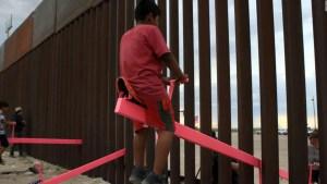 Niños de México y EE.UU. juegan con toboganes a través de la frontera