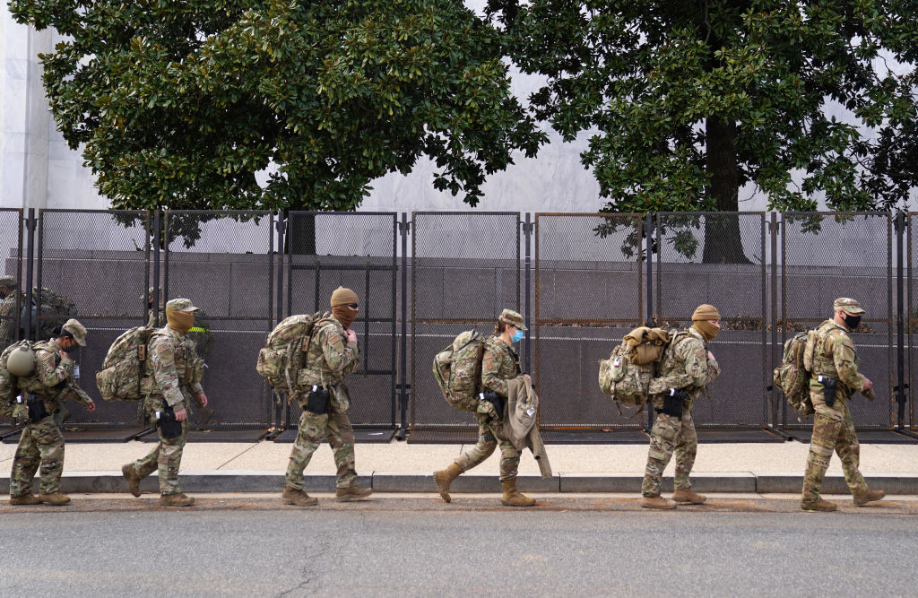 WASHINGTON, DC - JANUARY 16: National Guard troops march by security fencing near the U.S. Capitol on January 16, 2021 in Washington, DC. After last week's riots at the U.S. Capitol Building, the FBI has warned of additional threats in the nation's capital and in all 50 states. According to reports, as many as 25,000 National Guard soldiers will be guarding the city as preparations are made for the inauguration of Joe Biden as the 46th U.S. President. (Photo by Eric Thayer/Getty Images)