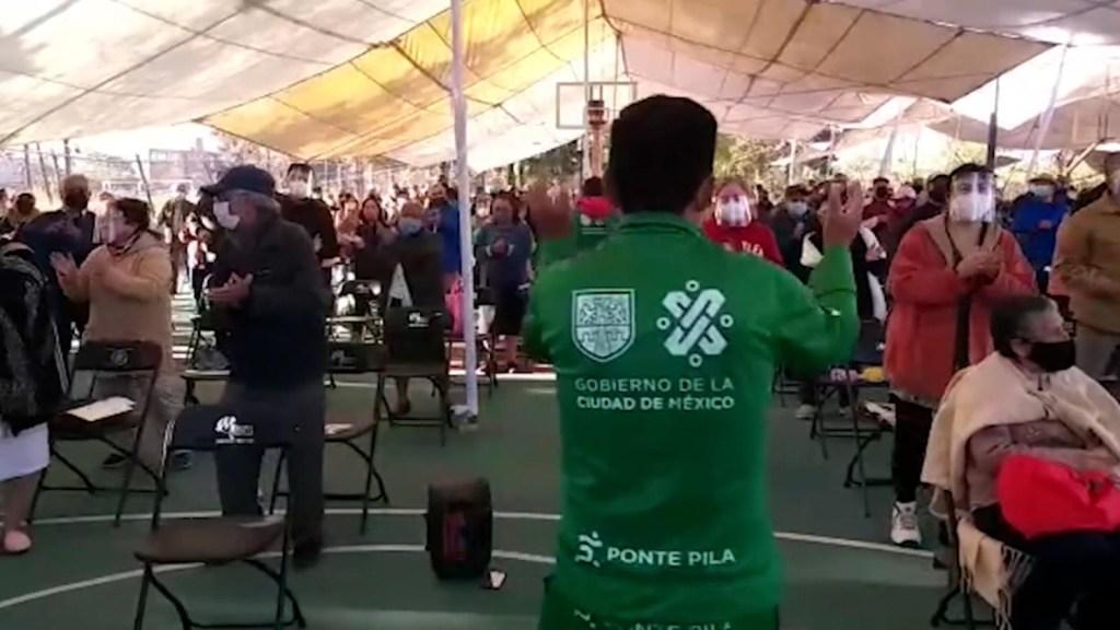 Adultos mayores bailan mientras esperan su vacuna