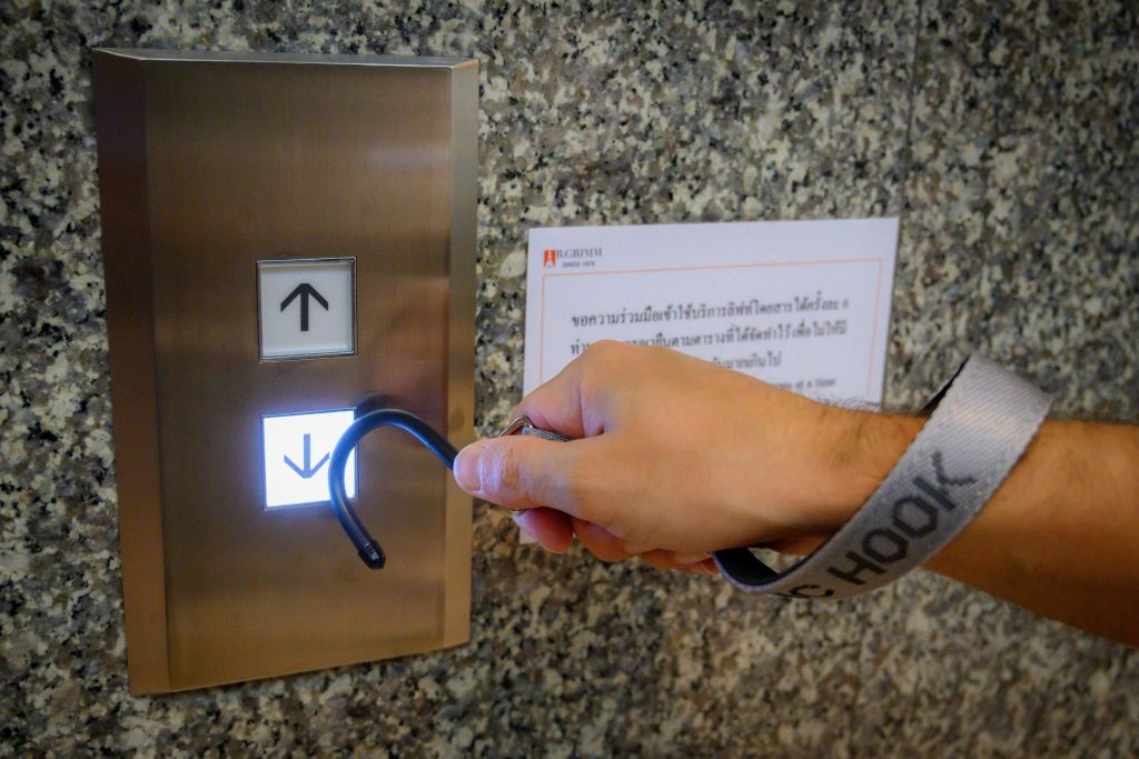 This photo illustration shows a hook tool on a strap, intended to enable hands free interactions with objects amid concern over the spread of the COVID-19 coronavirus, as it is used to press an elevator button in an office building in Bangkok on May 22, 2020. (Photo by Mladen ANTONOV / AFP) (Photo by MLADEN ANTONOV/AFP via Getty Images)