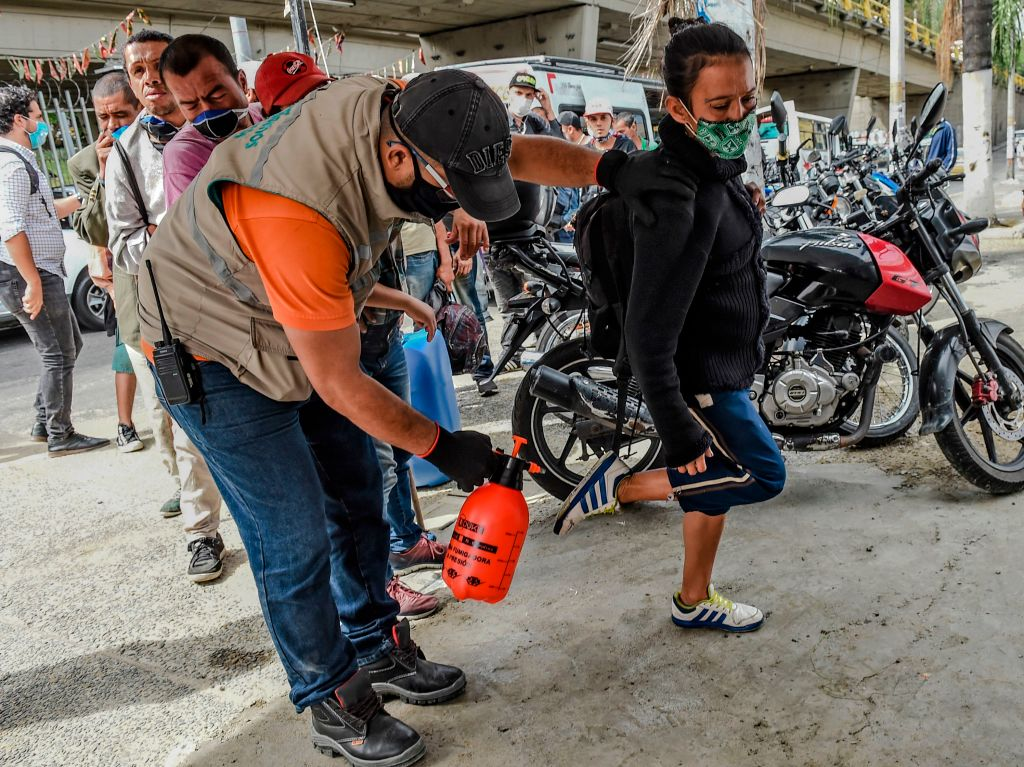 Funciona coronavirus An employee sanitizes the shoes of a woman before she enters an area provided for homeless people to take a shower and eat amid the COVID-19 pandemic in Medellin, Colombia, on June 23, 2020. (Photo by JOAQUIN SARMIENTO / AFP) (Photo by JOAQUIN SARMIENTO/AFP via Getty Images)