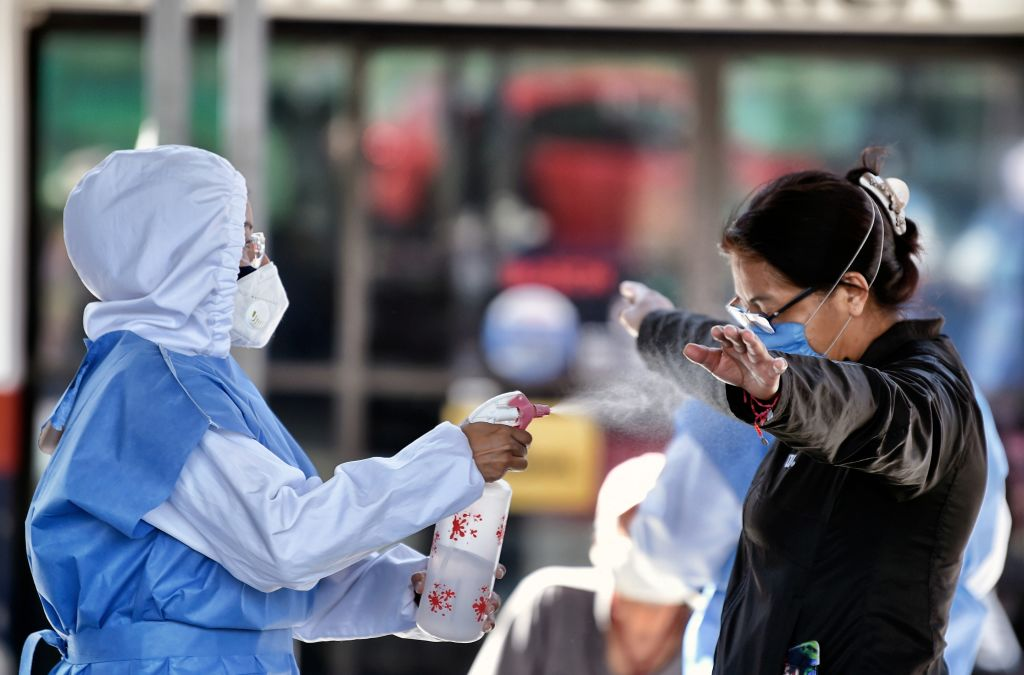 A health worker sanitizes a woman who waits for a COVID-19 rapid antigen test at a temporary health tent in Mexico City, on February 12, 2021. (Photo by ALFREDO ESTRELLA / AFP) (Photo by ALFREDO ESTRELLA / AFP via Getty Images)