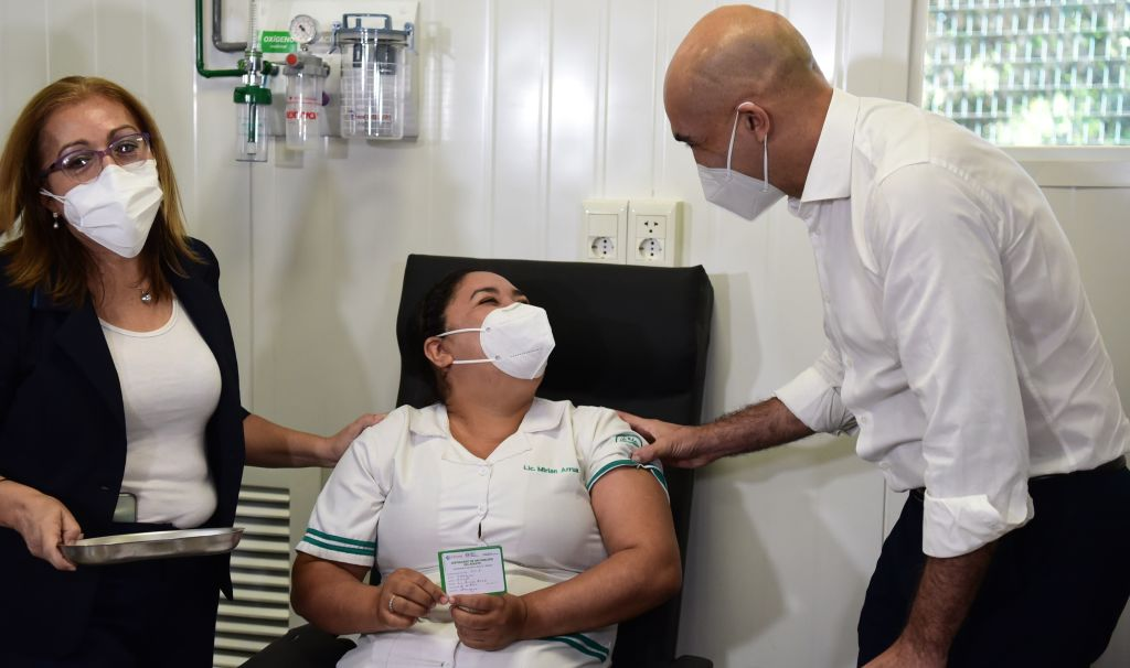 Vacunación paraguay Paraguay's Health Minister Julio Mazzoleni (R) talks to nurse Mirian Arrua after administering her the first dose of the Russian Sputnik V coronavirus vaccine, at the Itaugua National Hospital in Itagua, Paraguay, on February 22, 2021, amid the COVID-19 pandemic. - Last week, a first batch of 4,000 doses of Russian Sputnik V vaccines against COVID-19 arrived in Paraguay, with workers of respiratory therapy units the first to be immunized. (Photo by Norberto DUARTE / AFP) (Photo by NORBERTO DUARTE/AFP via Getty Images)