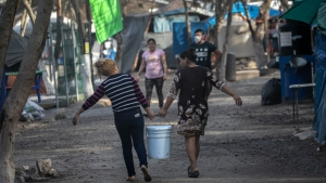 MATAMOROS, MEXICO - FEBRUARY 23: Asylum seekers carry fresh water distributed at a migrant camp at the U.S.-Mexico border on February 23, 2021 in Matamoros, Mexico. U.S. immigration authorities have begun allowing some asylum seekers with active cases into the U.S. in a reversal of the Trump administration's 'Remain in Mexico' immigration policy. (Photo by John Moore/Getty Images)