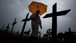 TOPSHOT - A worker wearing a protective suit and carrying an umbrella walks past the graves of COVID-19 victims at the Nossa Senhora Aparecida cemetery, in Manaus, Brazil, on February 25, 2021. - Brazil surpassed 250,000 deaths due to COVID-19. (Photo by MICHAEL DANTAS / AFP) (Photo by MICHAEL DANTAS/AFP via Getty Images)