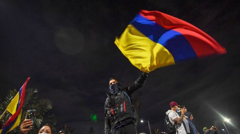 A man flutters a Colombian flag during a protest against President Ivan Duque's government in Bogota, on May 6, 2021. - Colombia's government on Thursday invited protest leaders to a dialogue in an attempt to calm tensions following more than a week of deadly demonstrations against President Ivan Duque. (Photo by Juan BARRETO / AFP) (Photo by JUAN BARRETO/AFP via Getty Images)