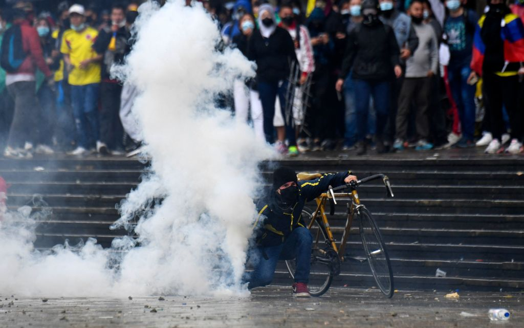Demonstrators clash with riot police during a protest against President Ivan Duque's government at the Bolivar square in Bogota on May 5, 2021. - Thousands of people returned to the streets of Colombia on Wednesday in rejection of the government of Ivan Duque, who has completed a week of pressure with demonstrations that turned violent in some cities and left some twenty people dead. (Photo by Juan BARRETO / AFP) (Photo by JUAN BARRETO/AFP via Getty Images)